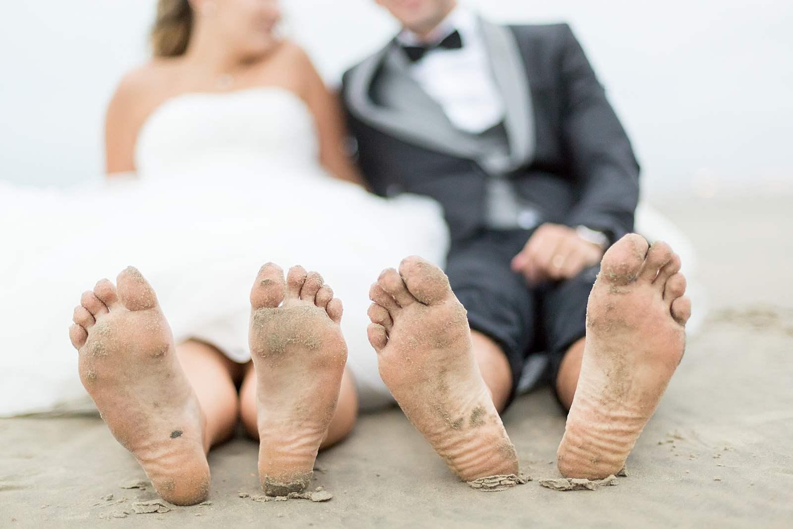 portrait des pieds des jeunes mariés pleins de sable.