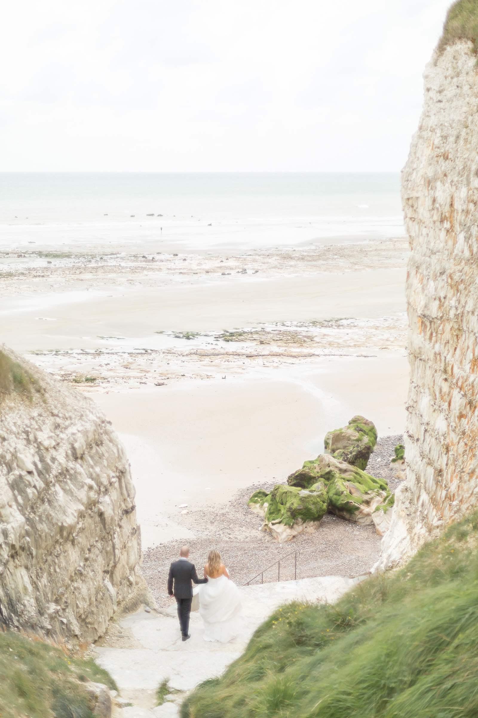 photographie de mariage. les mariées descendent les marches pour accéder à la plage de la falaise de vasterival