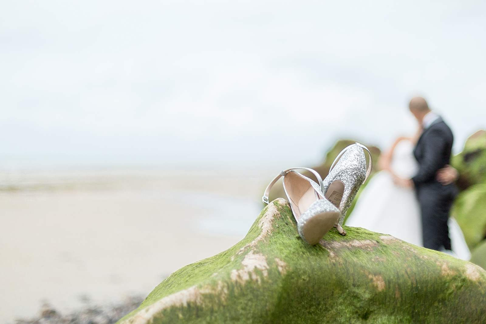 détails de mariage. les chaussures de la mariée sur un rocher a marée basse. les jeunes mariés s'embrassent en arrière plan