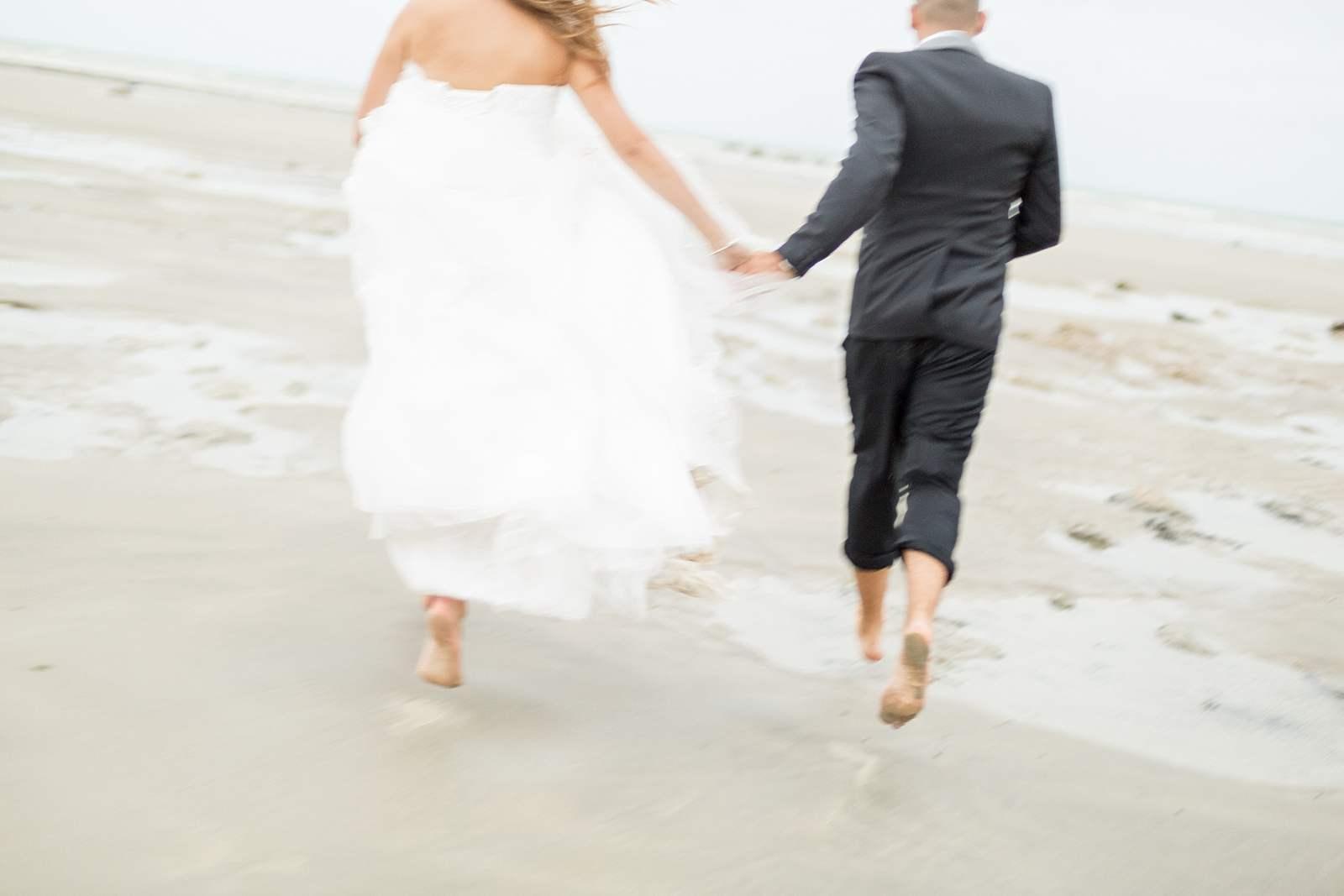 les mariés courent sur la plage main dans la main lors de la séance photo de couple en normandie.