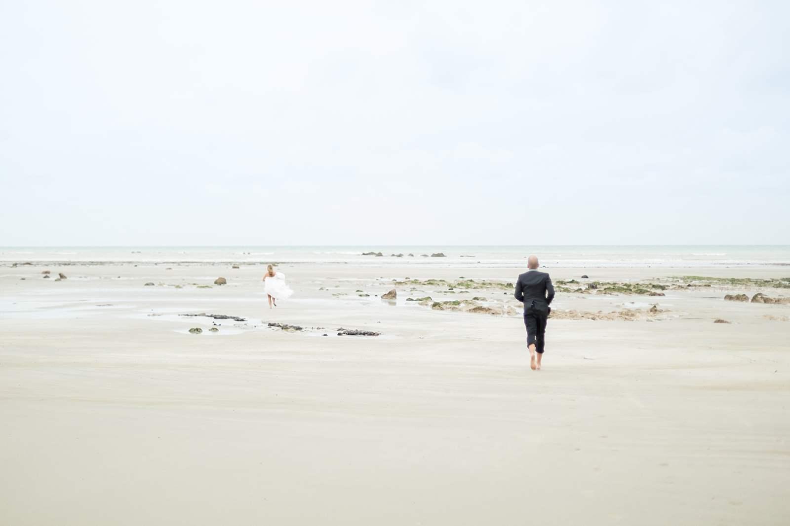 les mariés se courent après sur la plage de normandie. ils sont pieds nus dans le sable. la marée est basse.