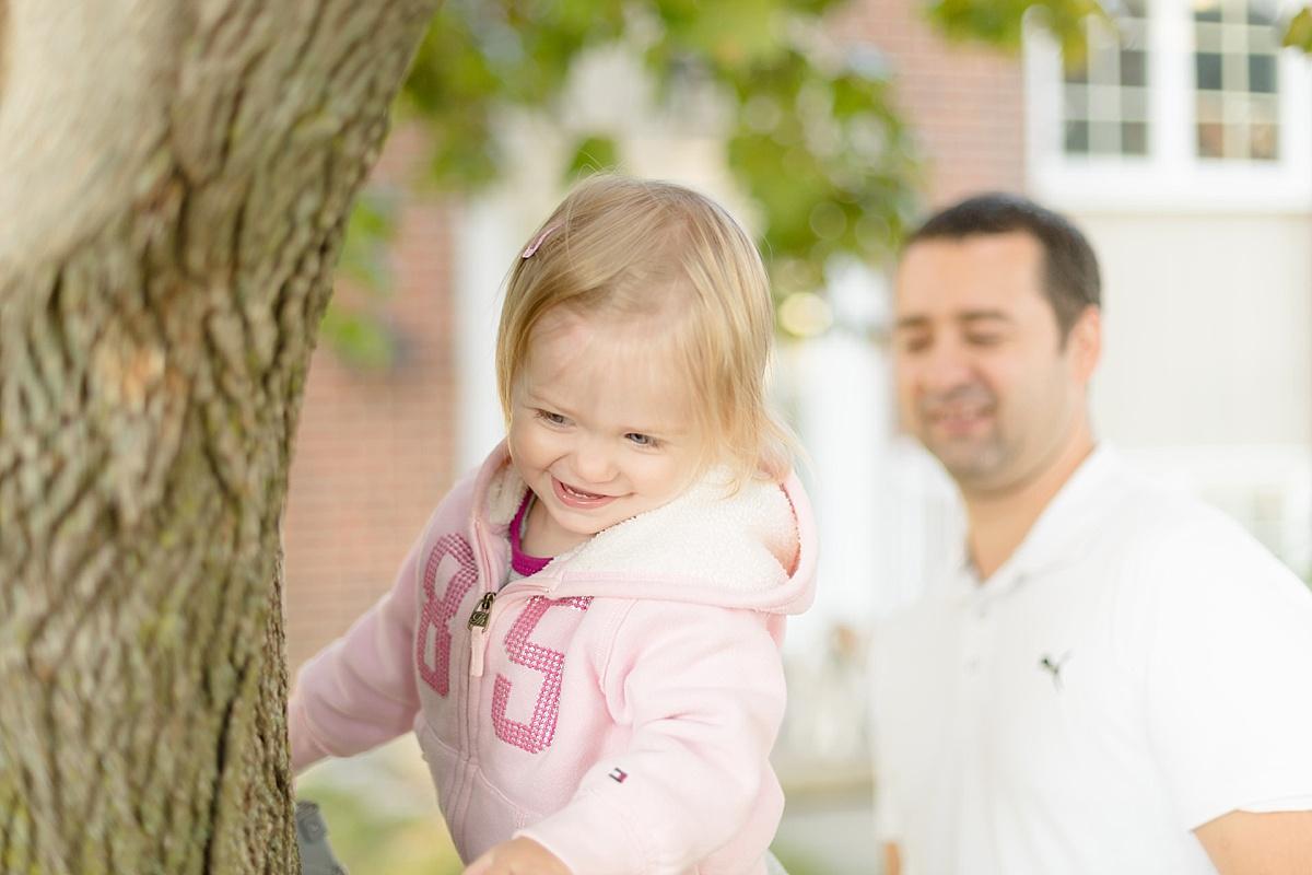 Papa et sa fille jouent à grimper aux arbres pendant la séance famille