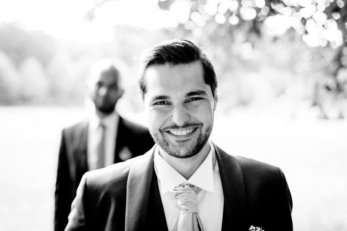 Portrait du marié. mariage château de champlâtreux. portrait noir et blanc du marié qui sourit