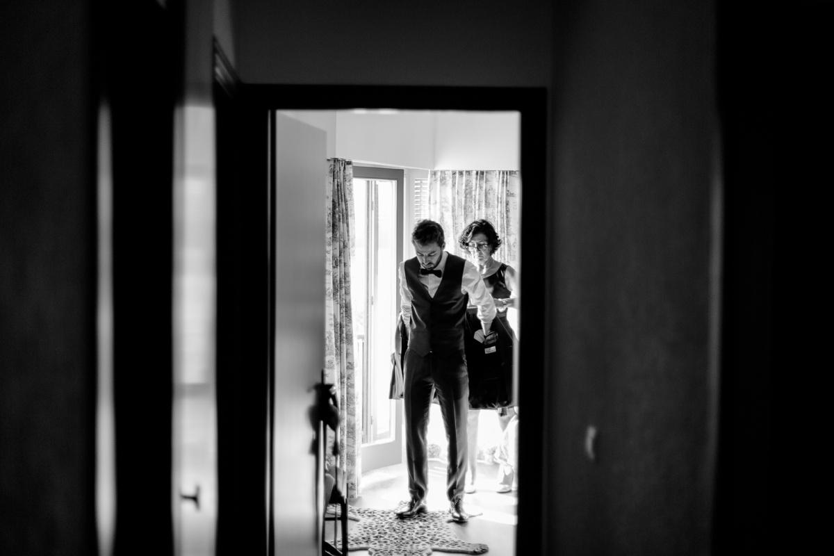 Fin des préparatifs du marié noir et blanc dans l'encadrement de porte