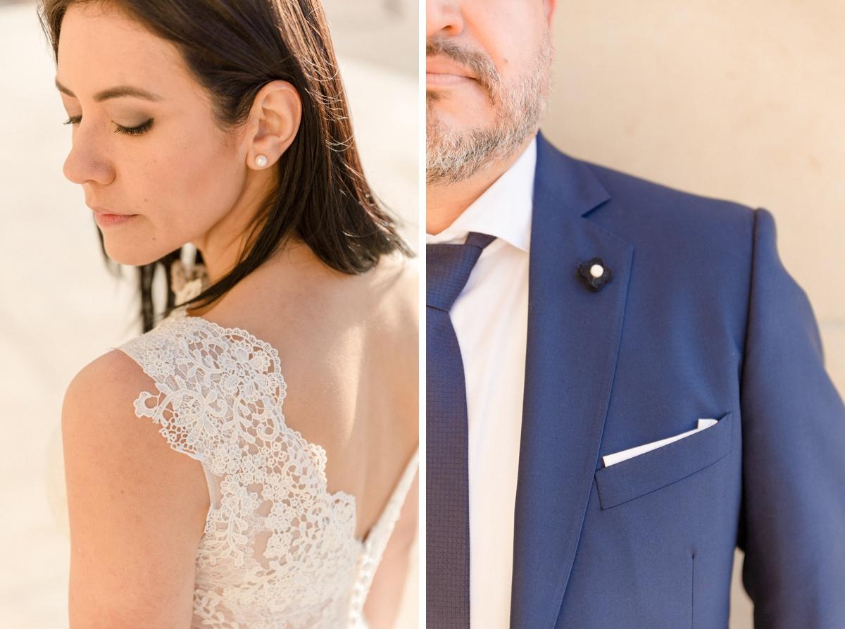 Photographie de détail dentelle robe de mariée et costume de marié bleu foncé