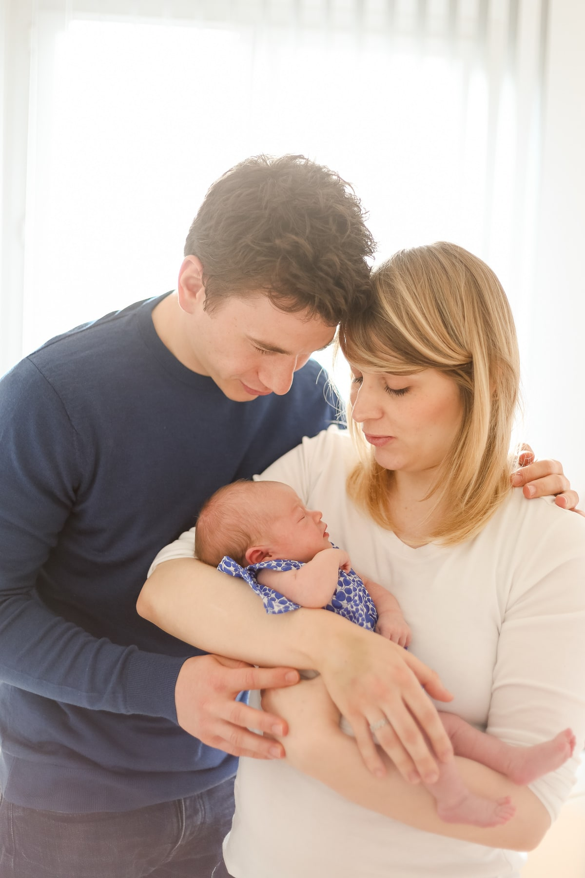 Photographie de portrait de famille avec un nouveau né. Papa enlace maman qui tient bébé dans ses bras