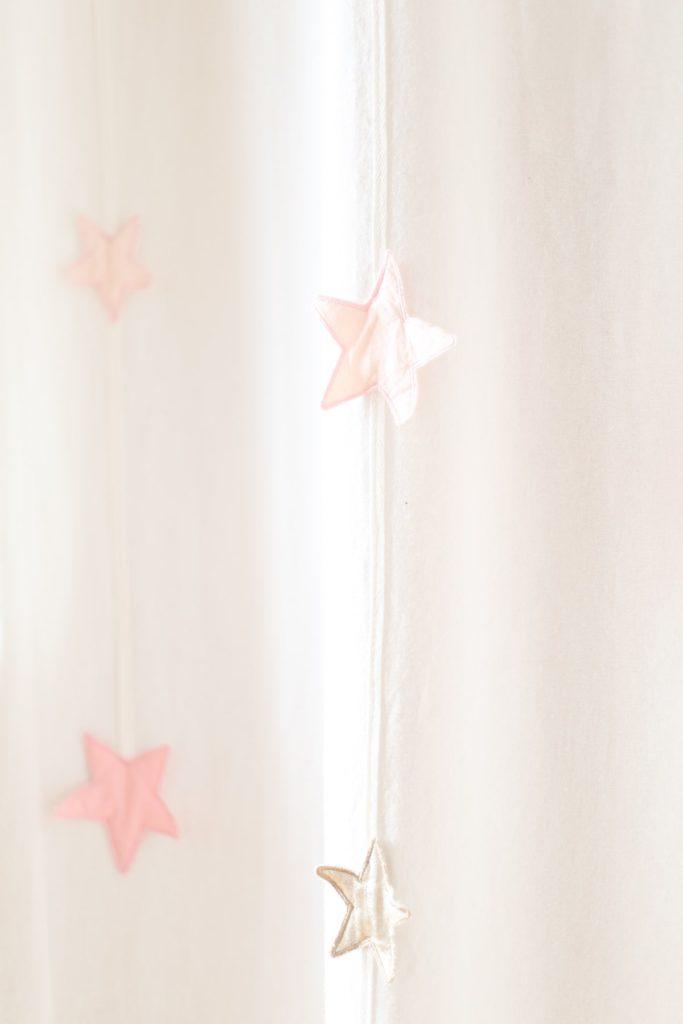 Photographie de détail d'un rideau de chambre d'enfant avec des étoiles roses