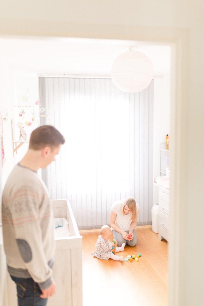 Maman qui joue avec son enfant pendant que papa surveille depuis la porte. seance photo en famille