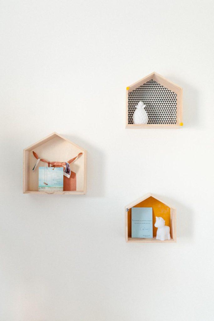 Photographie de décoration de chambre d'enfants. Cabanes en bois fixées au mur et décoration.