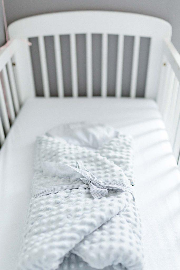 Lit de bébé blanc et couverture de lit. Le lit de bébé est prêt.