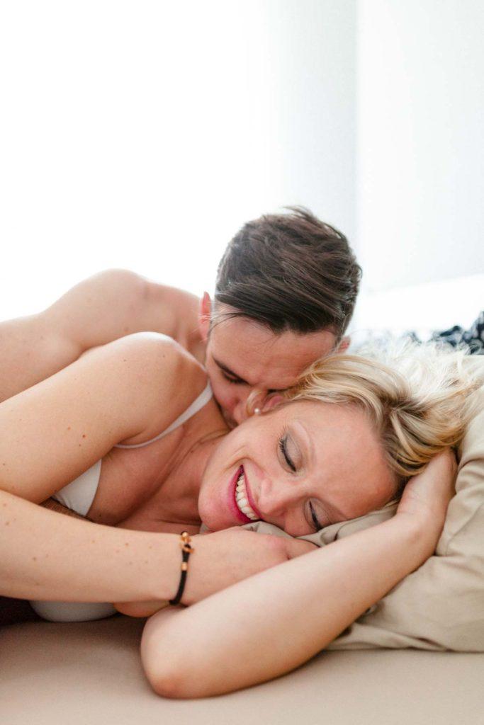 Couple heureux au réveil dans le lit. Photographie lumineuse en contrejour. Lumière naturelle.