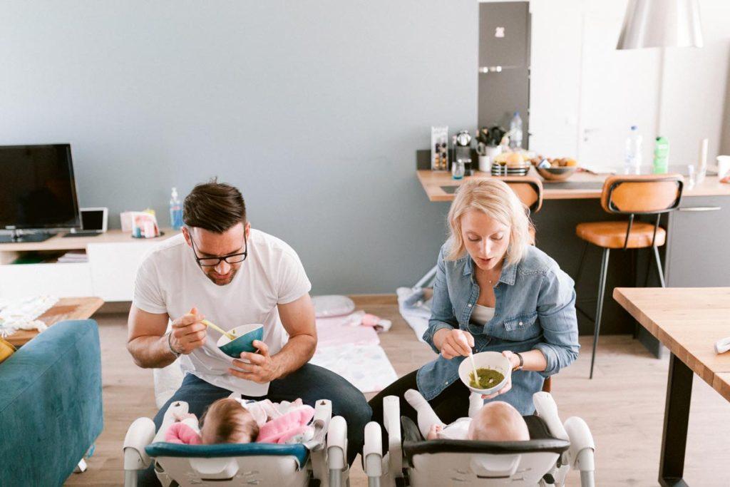 Repas en famille. Papa et maman donnent à manger aux jumelles installées sur leur chaise haute