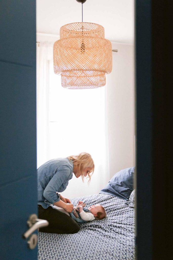 Maman joue avec sa fille sur le lit parental pendant que papa joue de son coté avec l'autre jumelle