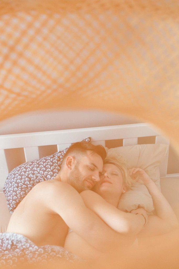 un couple s'enlace dans le lit à leur réveil. Couple en peau à peau