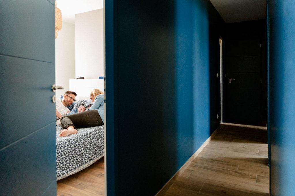 Parents et enfants sont réunis une dernière fois dans la chambre parental pour un moment complice en famille. Je les aperçoit par la porte entrouverte dans le couloir bleu roi.